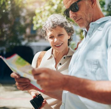 Close up shot of active senior on a vacation reading a city map. Mature man and woman using city map for directions in the city.